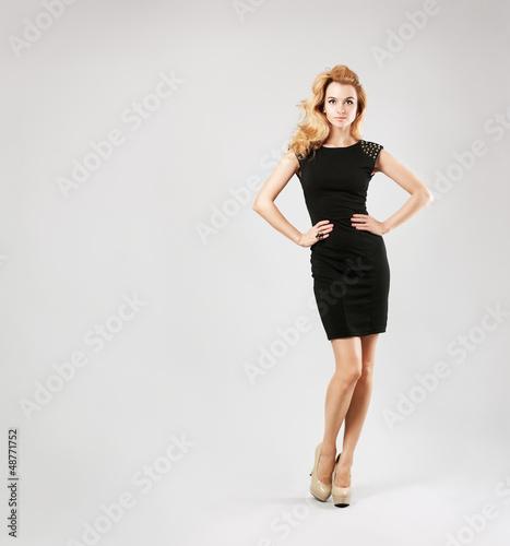 Beautiful Woman in Black Dress on Gray Backgound