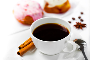Cup of coffee and sweets on white background