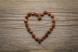 Heart shape made from coffee beans on wooden table.