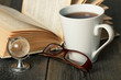 Warm tea cup on wooden table with old book, glasses and globe