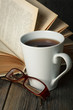 Warm tea cup on wooden table with old book and glasses.