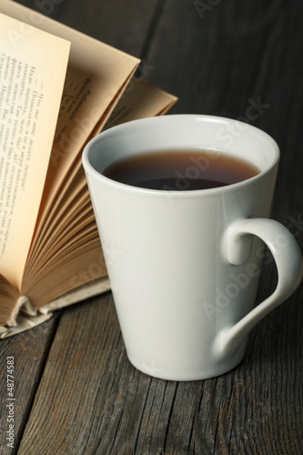 Cup of tea with old opened book on wooden table.