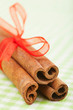cinnamon sticks with red ribbon on green tablecloth