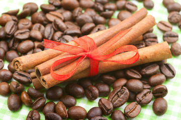 cinnamon sticks with red ribbon on coffee beans