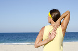 Mature woman stretch exercise beach