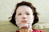 Portrait  woman applying rejuvenating facial mask on her face poster