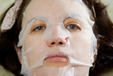Portrait  close-up woman applying rejuvenating facial mask on h poster