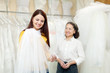 Girl chooses bridal veil at shop of wedding fashion