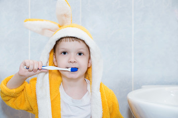 child brushing his teeth in the bathroom