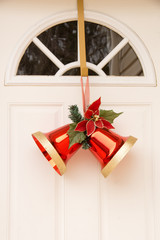 Two christmas red bells on white door