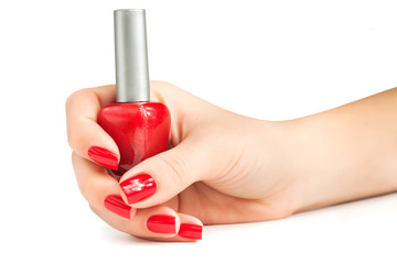 Hand with red nail polish bottle isolated