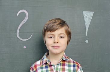 Kind vor Schultafel zwischen Fragezeichen und Ausrufezeichen
