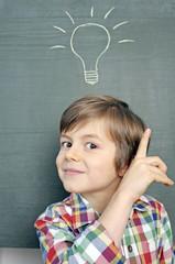 Kind mit Idee-Symbol vor Schultafel