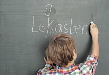 Kind schreibt falsch an Schultafel