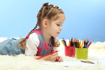 cute little girl playing with multicolor pencils,