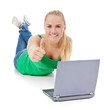 Attraktive junge Frau mit Laptop zeigt Daumen hoch