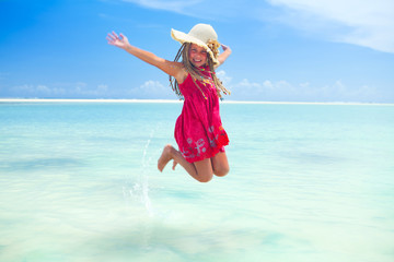 girl jumping in tropical sea