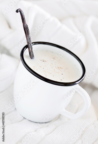 Mug of hot milk with vanilla on white knitted blanket