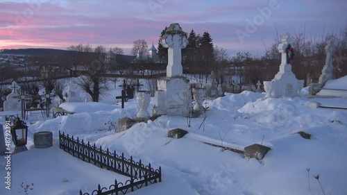 Young woman walking in cemetery during winter time