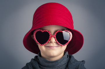 Smiling kid wearing heart glasses and red vintage hat.