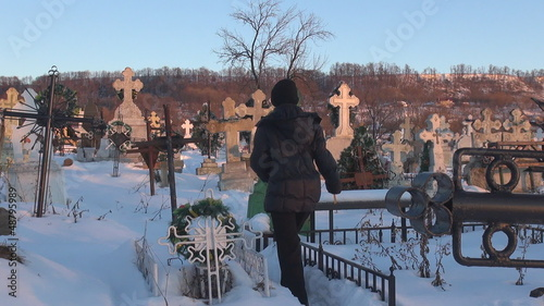 Young woman in cemetery during winter time
