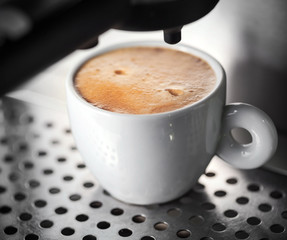 White ceramic cup of fresh espresso with nice foam in the coffee