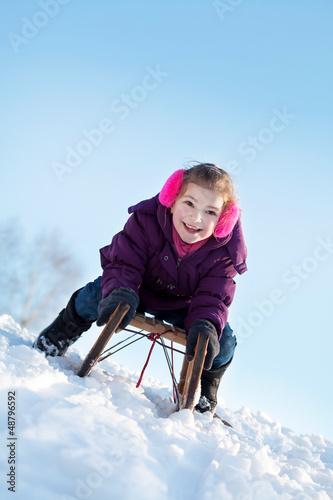 Mädchen beim rodeln an einem sonnigen Tag