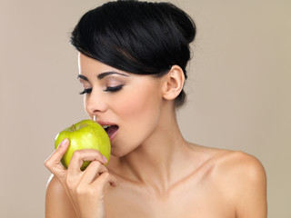 Beautiful woman eating a green apple
