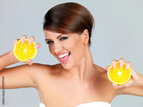 Playful woman with two orange halves