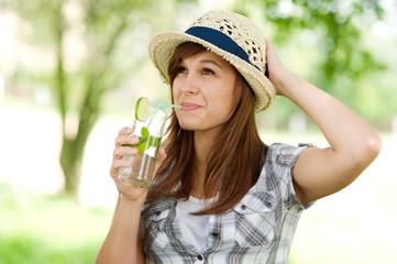 Young woman drinking mojito
