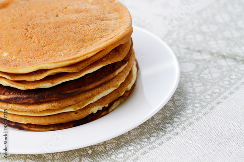 White plate with pankakes stack on the kitchen  table