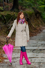 Cute young woman with umbrella wearing rubber boots