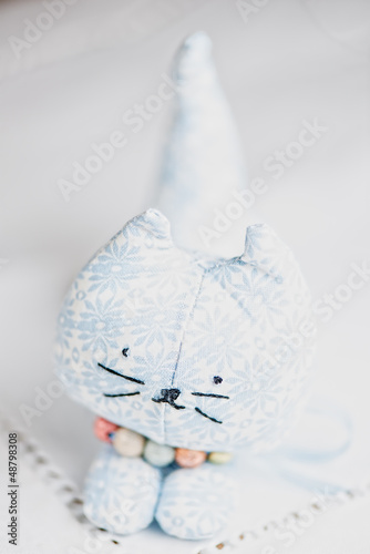 Homemade toy cat on white cloth