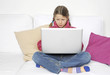 Kind arbeitet konzentriert an Laptop