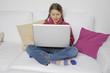 Mädchen mit Laptop auf Couch