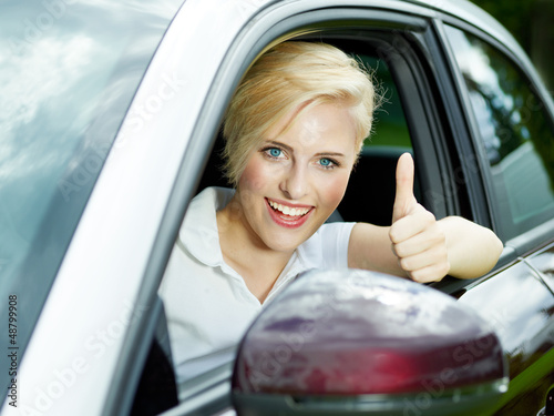 Beautiful woman shows thumbs up in her new car