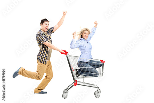 Full length portrait of a young man pushing a woman in a shoppin