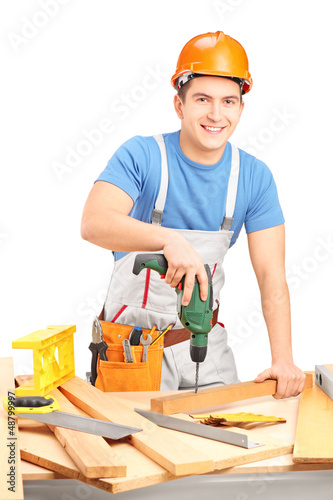 Male worker with a hand drilling machine in a workshop