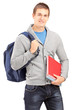 Smiling male student holding backpack and books