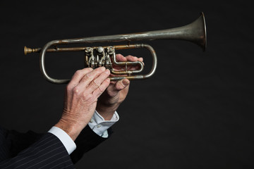 Closeup of senior hands holding trumpet.