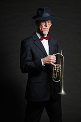 Senior jazz musician. Trumpet player. Studio shot.