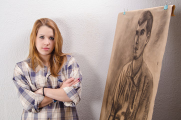 Young female artist posing beside her artwork
