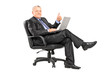 Businessman sitting in an armchair with a laptop and giving a th