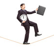 Businessman holding clock and briefcase and walking on a rope