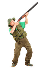 Full length portrait of a male hunter shooting with a rifle