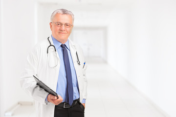 Male doctor holding a clipboard and standing in a hospital