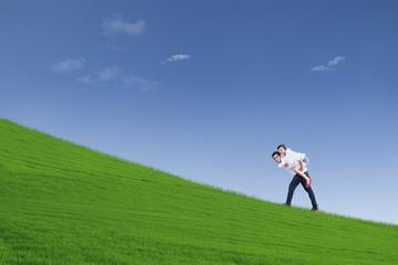 Guy giving piggyback ride under blue sky