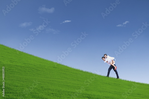 Guy giving piggyback ride under blue sky