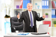 Businessman posing in his office and giving a thumb up