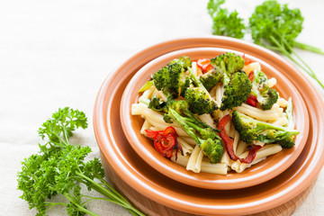 Delicious pasta with pepper and broccoli on a plate closeup
